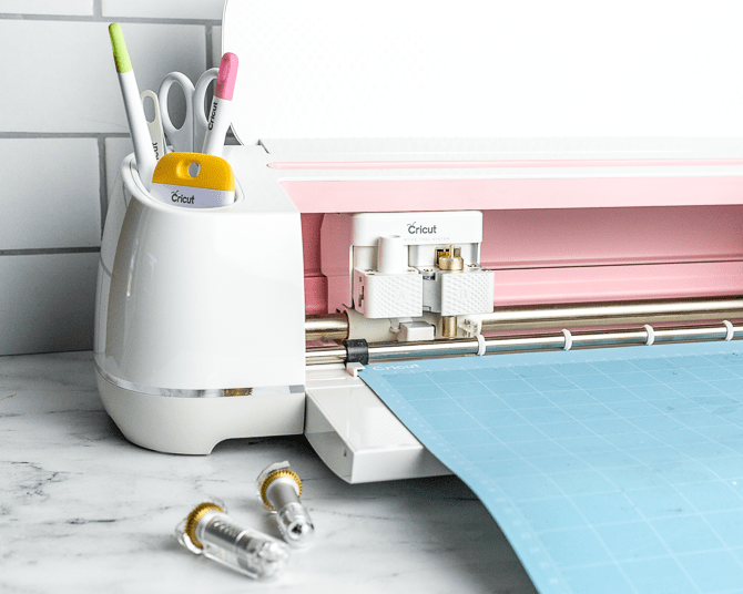 an open Cricut Maker cutting machine with a blue mat and assorted tools