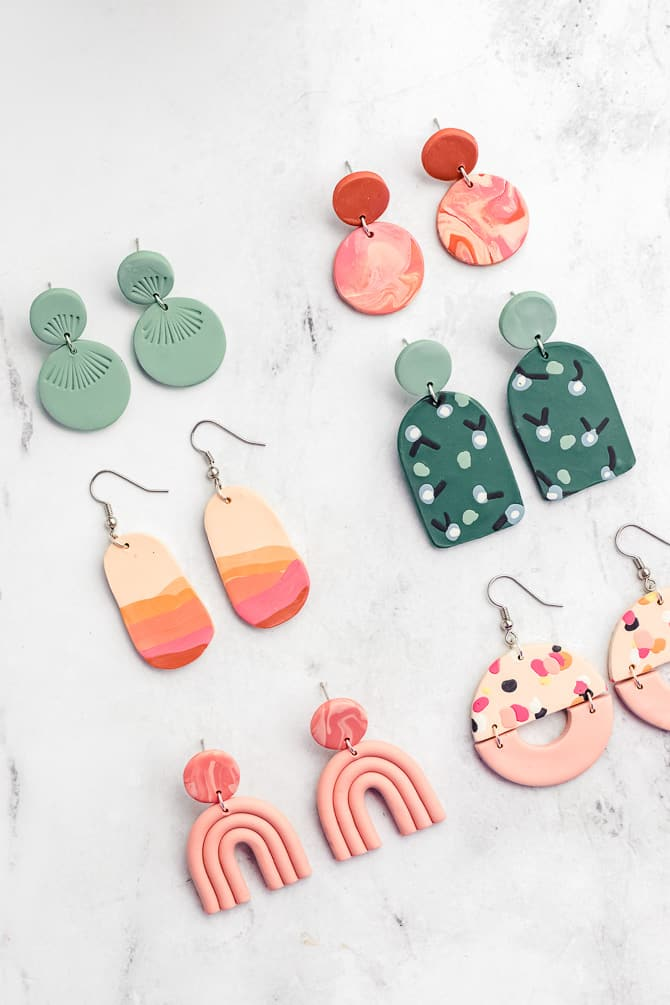variety of different polymer clay earring designs in pink and green colors