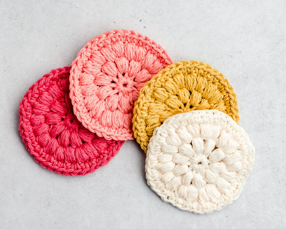 4 cotton crochet face round scrubbies in pink, gold and white colors of cotton yarn