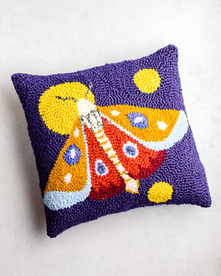 a finished punch needle pillow in blue and orange colors with a whip stitch edge.