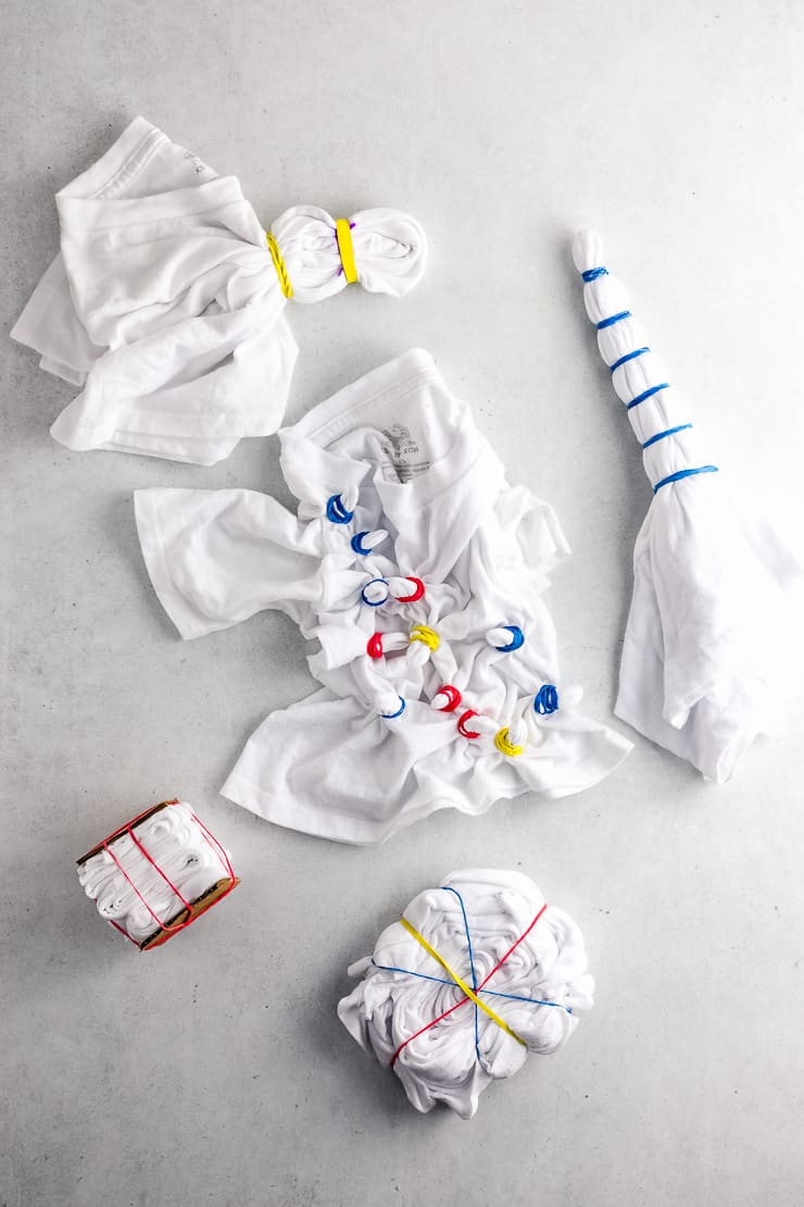 various shirts and socks folded up and tied with rubber bands in preparation for tie dye