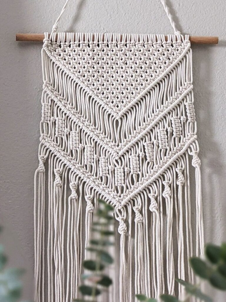 macrame wall hanging made with cream color cotton yarn hanging from a wooden dowel rod